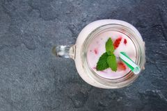 A top view on a mason jar with jogurt on a marble background. Food concept. A top view on a mason jar with jogurt and pieces of strawberries and green leaflets stock images