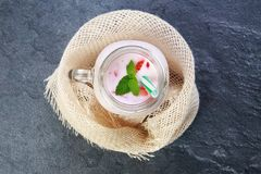 A top view on a mason jar with jogurt on a marble background. Food concept. A top view on a mason jar with jogurt and pieces of strawberries and green leaflets royalty free stock images