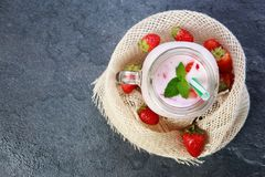 A top view on a mason jar with jogurt on a marble background. Food concept. A top view on a mason jar with jogurt and pieces of strawberries and green leaflets royalty free stock image
