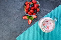 A top view on a mason jar with jogurt on a marble background. Food concept. A top view on a mason jar with tasty fresh jogurt and strawberries in bowl on a stock image