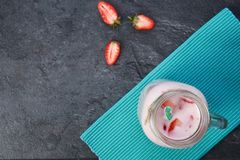 A top view on a mason jar with jogurt on a marble background. Food concept. A top view on a mason jar with tasty fresh jogurt and three pieces of strawberries royalty free stock images