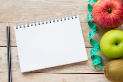 Top view with measuring tape,apple,pencil and notebook on wood table background stock photos