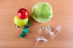 Top view on measuring tape, vacuum massagers, apples and cabbage on wooden table Stock Images