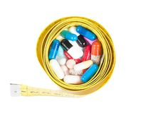 Top of view of medical blue pills in front of measure tape, concept for diet Royalty Free Stock Photo
