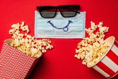 Top view of medical mask with smile near sunglasses and buckets with popcorn