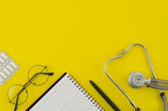 Top view medical stethoscope and white calendar on yellow background. Schedule doctor appointment visit. Medicine. Concept. Flat lay mock-up stock images