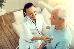 Top view of medical worker listening to heart beating. Healthy patient. Selective focus on a serene female nurse sitting on a sofa and smiling slightly while royalty free stock photography