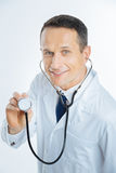 Top view on medical worker posing with stethoscope. Restoring human health. Mature male doctor looking into the camera with a friendly smile on his face while royalty free stock photos