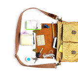 Top view,Men Bag with essentials for modern men person on white table .leather bag, smartphone,power bank, notepad, book,keys, med royalty free stock photo