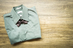 Top view Men's outfits with green shirt and tie on old wood tabl. E Royalty Free Stock Images