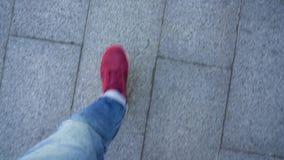 Top view of mens legs in red sneakers walking along the sidewalk stock video footage