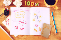 Top view of messy table with notebook with doodles, coffee cup, papers and keys. Royalty Free Stock Photos