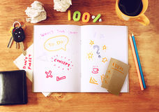 Top view of messy table with notebook with doodles, coffee cup, papers and keys. Royalty Free Stock Photography