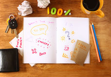 Top view of messy table with notebook with doodles, coffee cup, papers and keys. Royalty Free Stock Photo