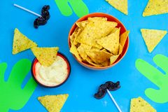 Mexican party table food and decorations corn chips nachos with sauce,paper cut cactuses and caramel moustaches on blue. Top view mexican party table food and royalty free stock photography
