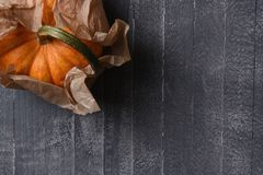 Decorative pumpkin wrapped in plain brown paper. Top view of a mini decorative pumpkin wrapped in plain brown paper. Horizontal with copy space stock photography