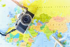 Top View of Miniature Airplane and Vintage Mirrorless Camera on World Map Background stock photo