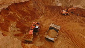Top view of mining equipment working at sand mine. Sand work. Top view of mining equipment working at sand mine. Crawler excavator pour sand in mining truck stock video
