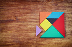Top view of a missing piece in a square tangram puzzle, over wooden table. Stock Photos