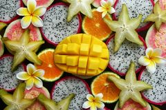 Top view on the mixed fresh and ripe tropical fruits with flowers o. Top view on the mixed fresh and ripe tropical fruits mango, tangerine, guava, dragon fruit stock photos