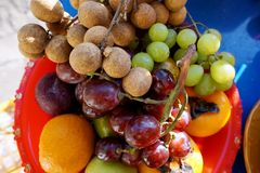 Top view of mixed fruit are fresh ripe red and green grape, longan, guava and persimmon stock photos
