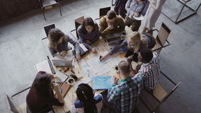 Top view of mixed race business team sitting at the table at loft office and working. Woman manager brings the document. Royalty Free Stock Image