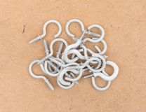 White coated cup hooks on a pressed board. Top view mixed small and large white coated metal cup hooks atop a brown pressed board Royalty Free Stock Photography