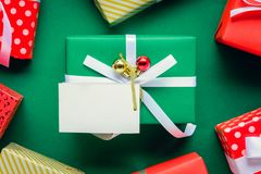 Top view mock up white text label and gift boxes on the green ta. Ble with the holiday season Royalty Free Stock Photos
