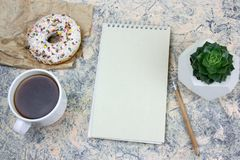 Mock up notebook with blank white paper sheet ,coffee cup and donut. Top view mock upnotebook with blank white paper sheet ,coffee cup and donut stock images