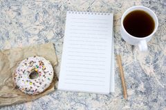Mock upnotebook with blank white paper sheet ,coffee cup and donut. Top view mock upnotebook with blank white paper sheet ,coffee cup and donut stock photography