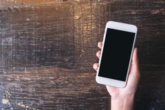 Top view mockup image of hand holding white mobile phone with blank black desktop screen on wooden table. In cafe Stock Photo