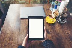 Top view mockup image of hands holding black tablet pc with blank white desktop screen with laptop and coffee cups on wooden table Royalty Free Stock Images