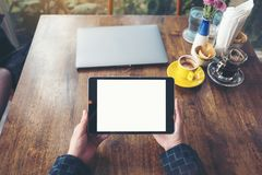 Top view mockup image of hands holding black tablet pc with blank white desktop screen with laptop and coffee cups on wooden table. In cafe Stock Photo