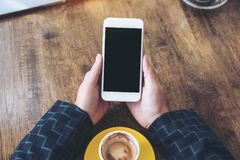 Top view mockup image of hands holding white mobile phone with blank black desktop screen and coffee cup on wooden table in cafe. Background Royalty Free Stock Photos