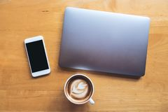 Top view mockup image of a white mobile phone with blank black desktop screen with laptop and coffee cup Stock Photos