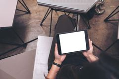 Top view mockup image of a woman holding black tablet pc with blank white screen stock image