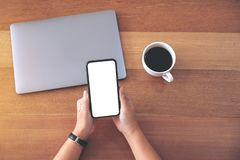A woman holding and using black mobile phone with blank white desktop screen with coffee cup and laptop stock images