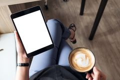 A woman sitting cross legged and holding black tablet pc with blank white desktop screen while drinking coffee in cafe. Top view mockup image of a woman sitting Stock Images