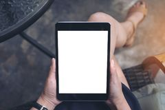 Top view mockup image of a woman sitting crossed legs holding black tablet pc Stock Photo
