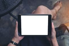 Top view mockup image of a woman sitting crossed legs holding black tablet pc Royalty Free Stock Photography