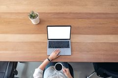 A woman using and touching on laptop touchpad with blank white desktop screen while drinking coffee on royalty free stock images