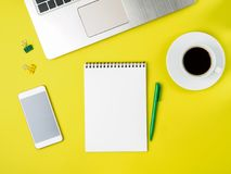 Top view of modern bright yellow office desktop with blank notepad, computer, smartphone. Mock up, empty space royalty free stock images