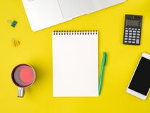 Top view of modern bright yellow office desktop with blank notep. Ad, computer, smartphone. Mock up, empty space stock photography