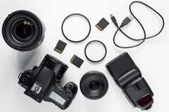 Top view of modern photo camera, lenses and equipment over white. Table background royalty free stock photos