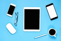 Top view, Modern workplace with tablet with smart phone placed on a pastel blue background. Royalty Free Stock Photos