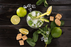 Top view of mojito cocktail in glass and fresh ingredients on dark wooden table top. Cocktail drinks concept Stock Photography