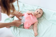Top view. Mom giving baby diaper change at home. Newborn, motherhood concept royalty free stock photo