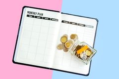 Top View money bottle with saving yellow label placed on the blank monthly plan notebook, coins spilling out isolated on white bac stock photo
