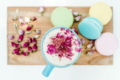 Top view on morning french macarons and a blue cappuccino cup with rose petals Royalty Free Stock Image