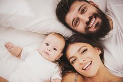 Top view. Mother and Father with Baby in Bed. stock images